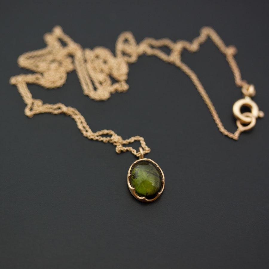 En grön turmalin satt i guld med en uppbruten sargfattning. Petronella Eriksson