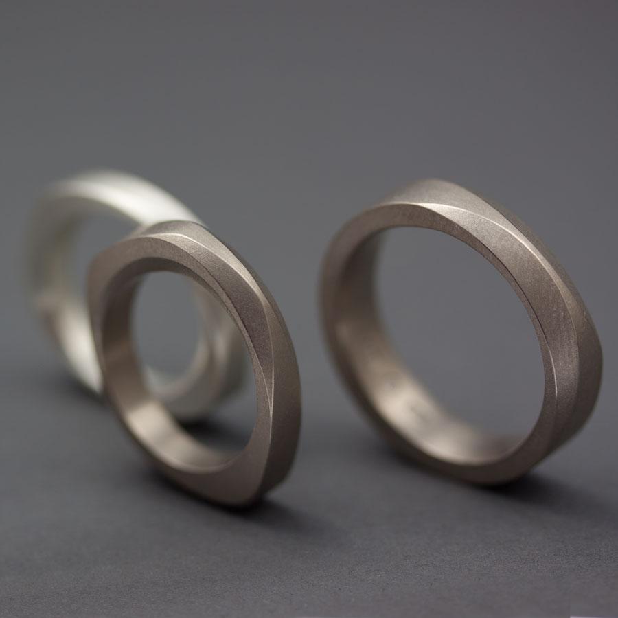 En grupp vigselringar, till höger mina geometriska ringar i vitguld och silver, till vänster en slät vitguldsring med kupad insida och två fasetter. Petronella Eriksson