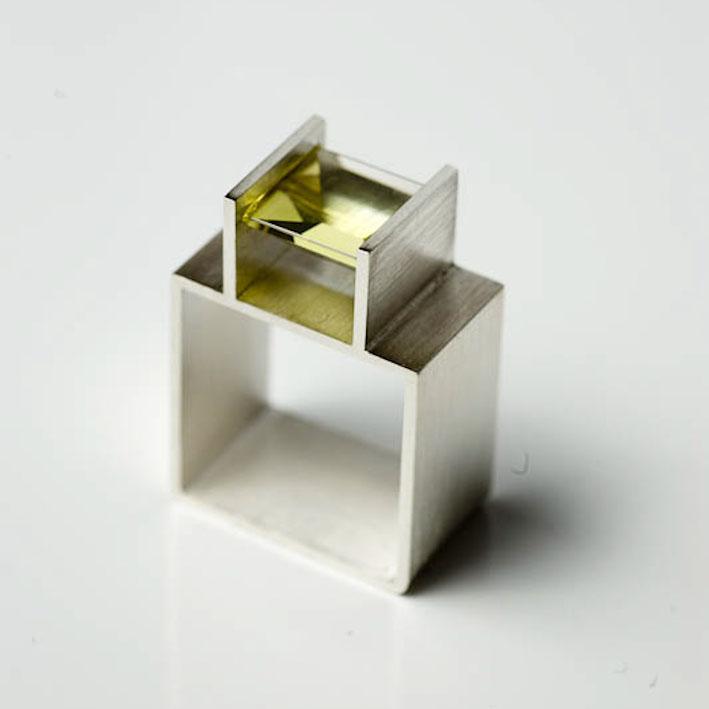 En fattning som också jobbar med att spänna fats stenen. Silver och pyridot. Pernilla Sylwan.