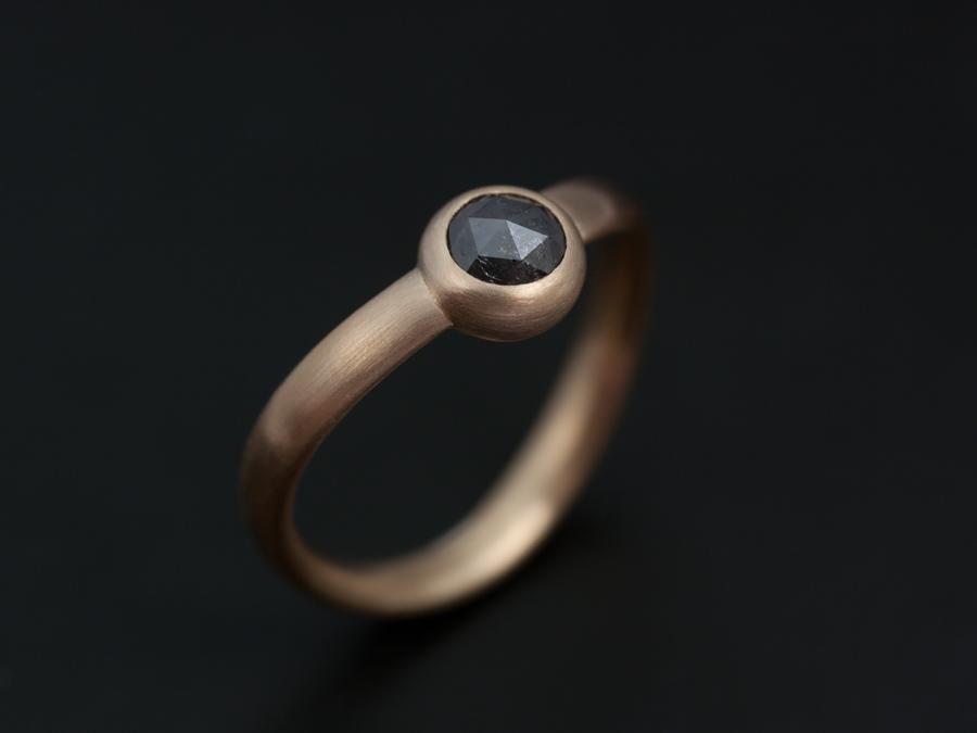 En rosenslipad diamant som satts med riven kant i en ögla av oval guldtråd. Petronella Eriksson.