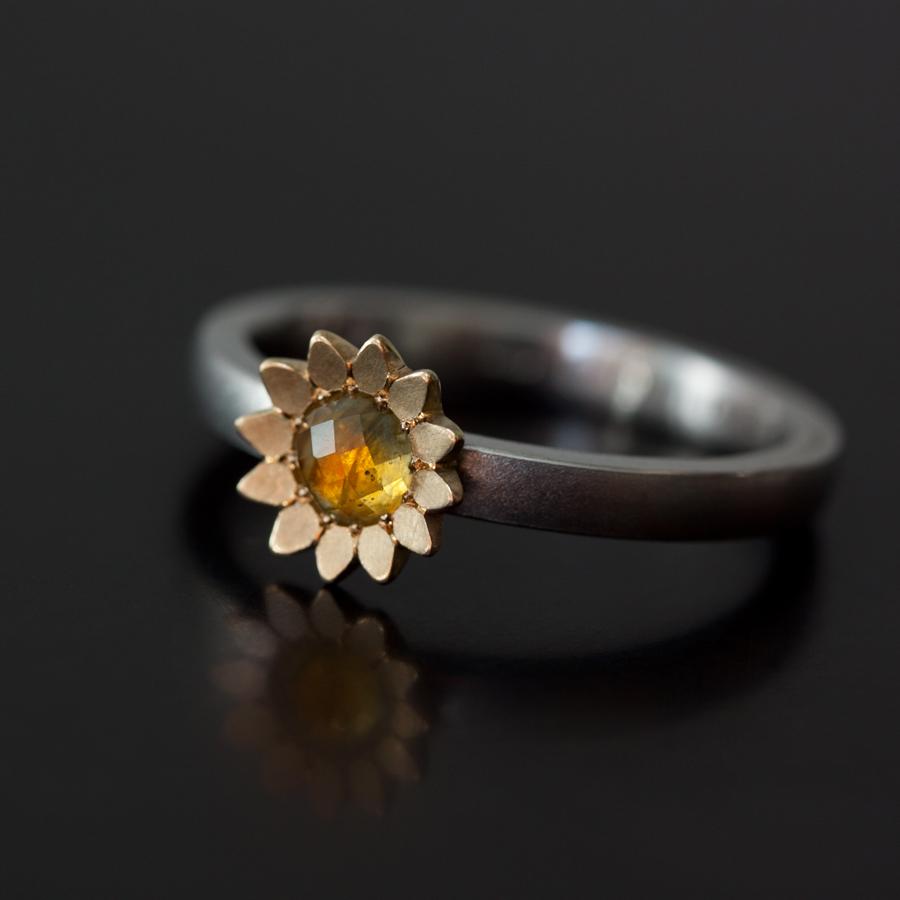 En solros av guld med en etisk safir på en vigselring av platina.Tillverkad av Petronella Eriksson